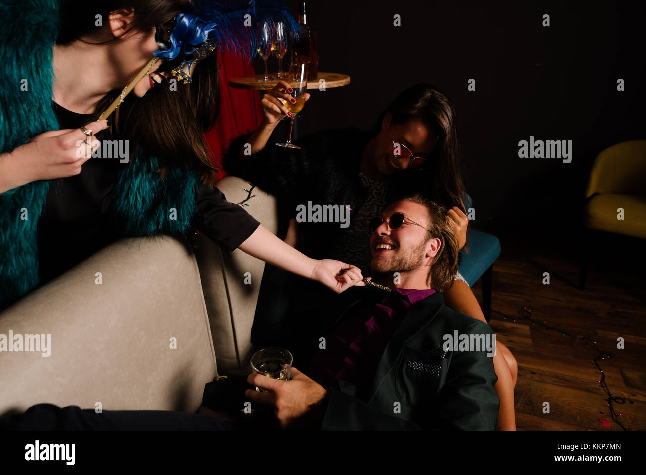 Masked woman seducing a couple at a party - Stock Image
