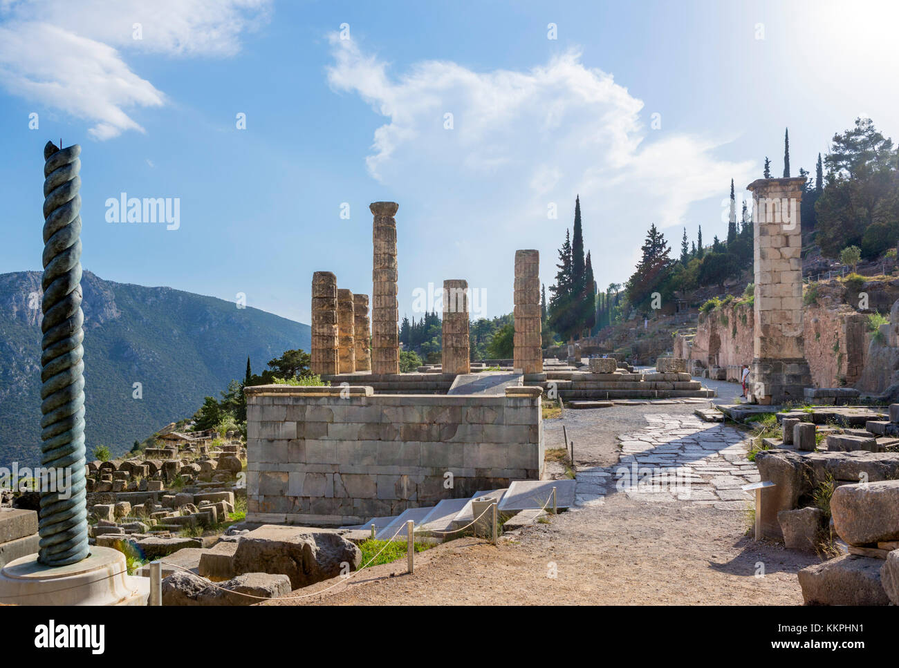 Temple of Apollo with a replica of the Serpent Column in the left foreground, Delphi, Greece - Stock Image