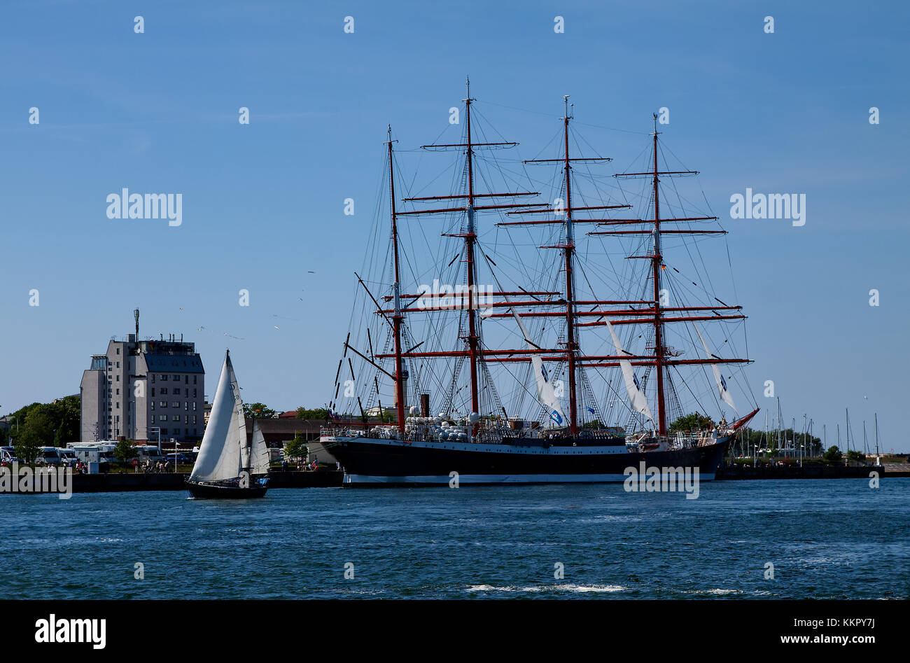 Big Sailor and small sailboat in harbour - Stock Image