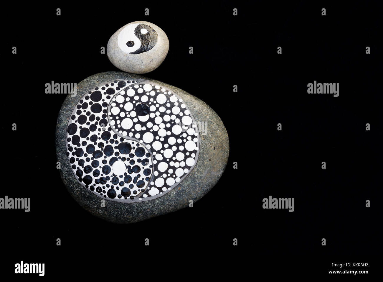 painted stones, yin and yang in black and white, Stone Art - Stock Image