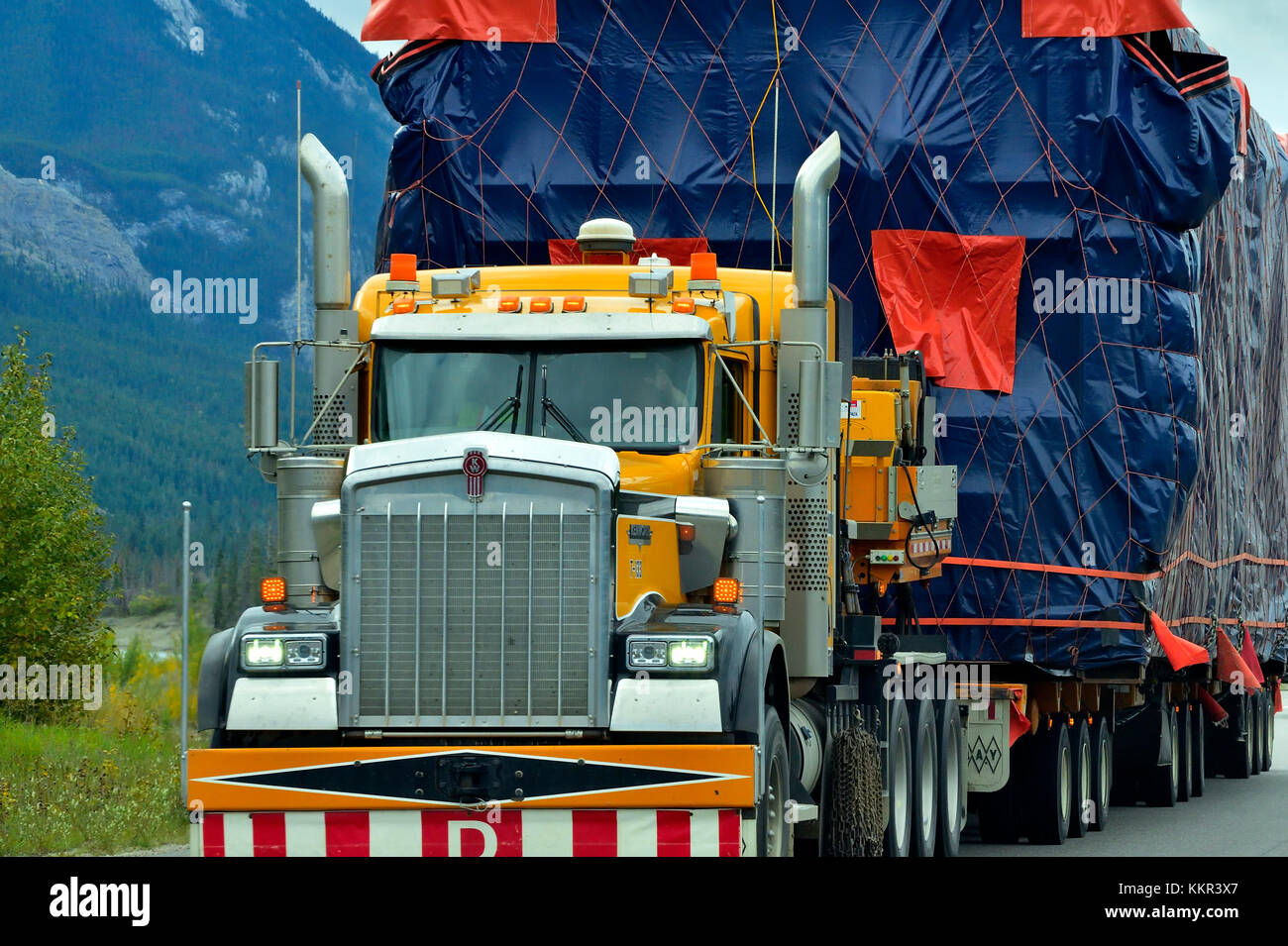 A close up of a semi truck with an oversize load traveling on an Alberta highway - Stock Image