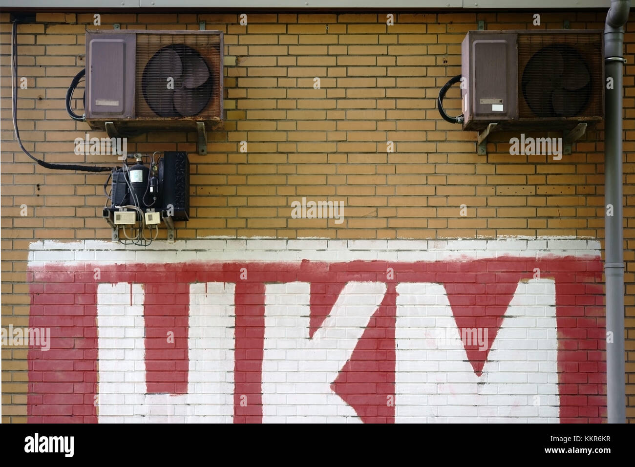 A painted barrack with brick walls and rusted ventilation. - Stock Image