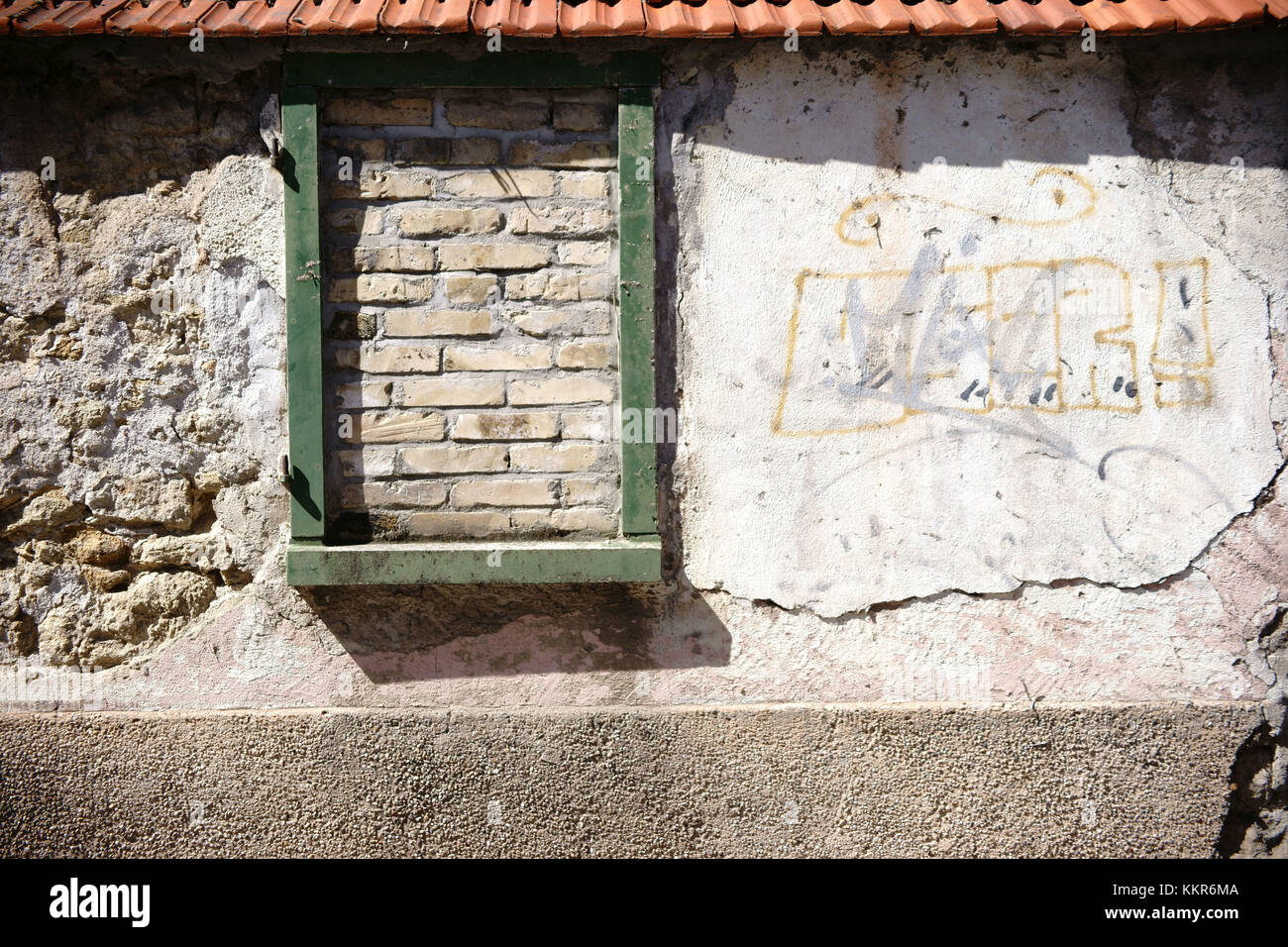 A rustic wall staggered and broken stones with roofing tiles and a bricked up window frame. - Stock Image