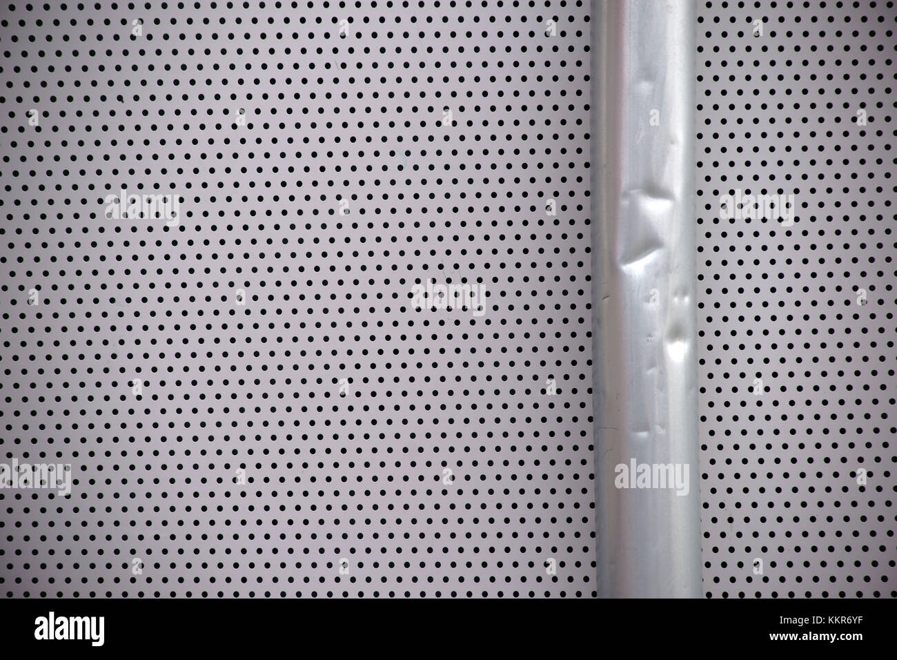 detail of a dented rain gutter on a perforated metal plate, close-up - Stock Image
