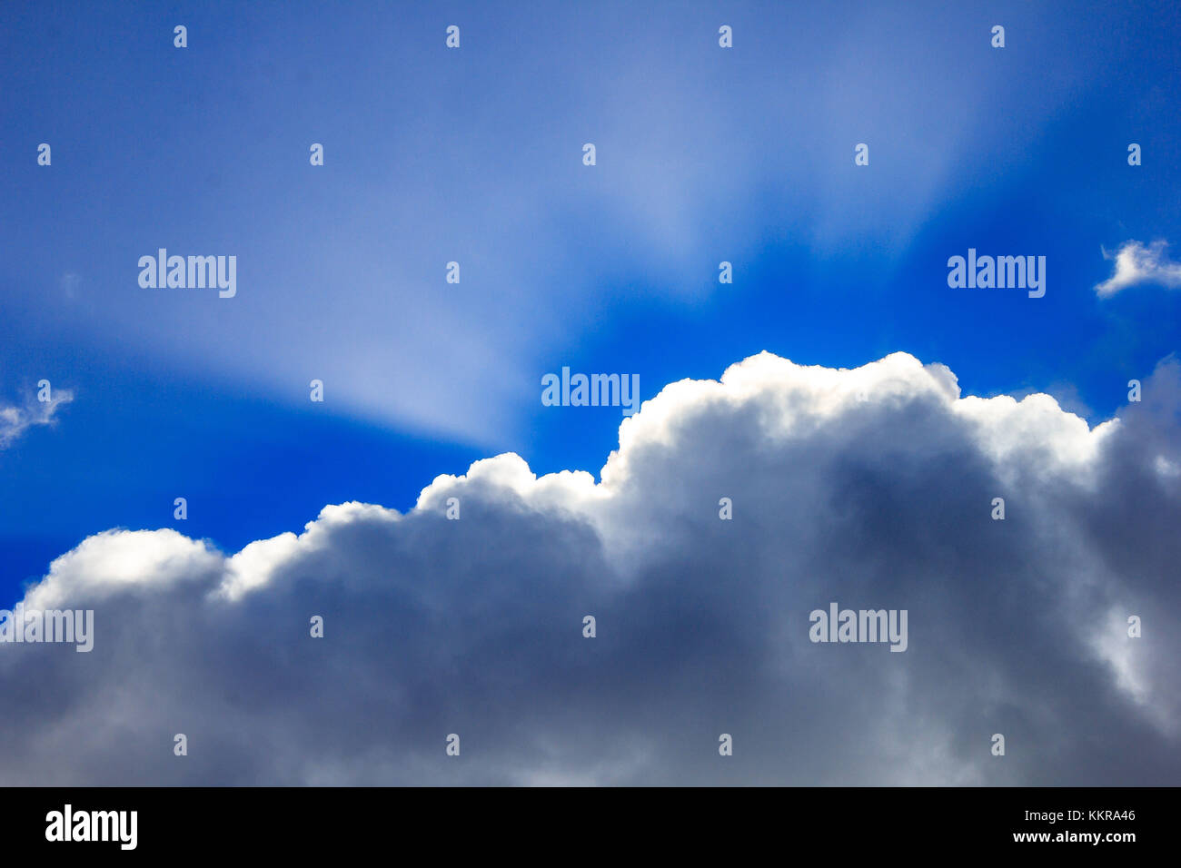 Sunlight shines through a cloud - Stock Image