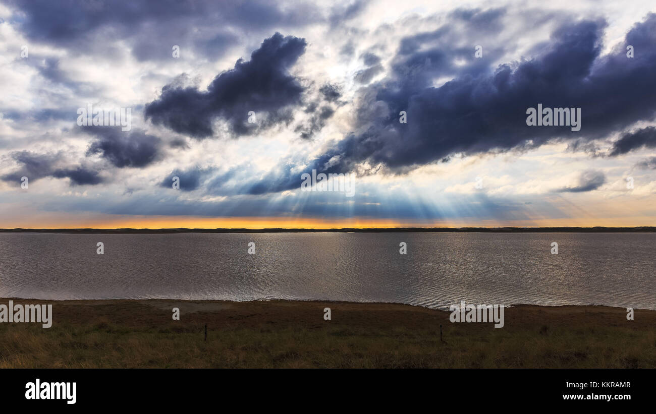 The sun shines through the clouds near Agger Tange - Stock Image