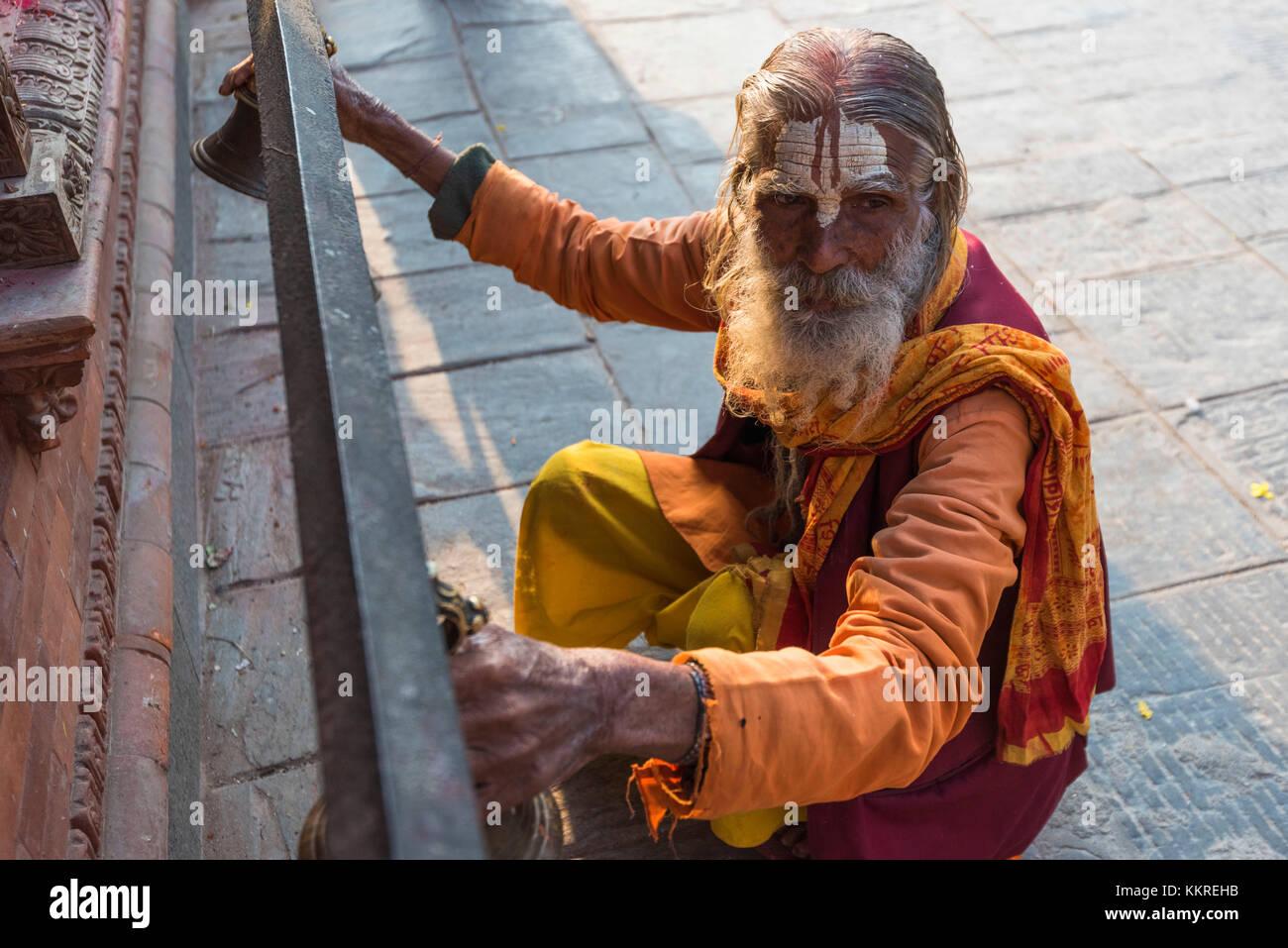 Budhanilkantha Temple, Katmandu, Nepal Sadhu plays bells for the ritual at Budhanilkantha temple - Stock Image