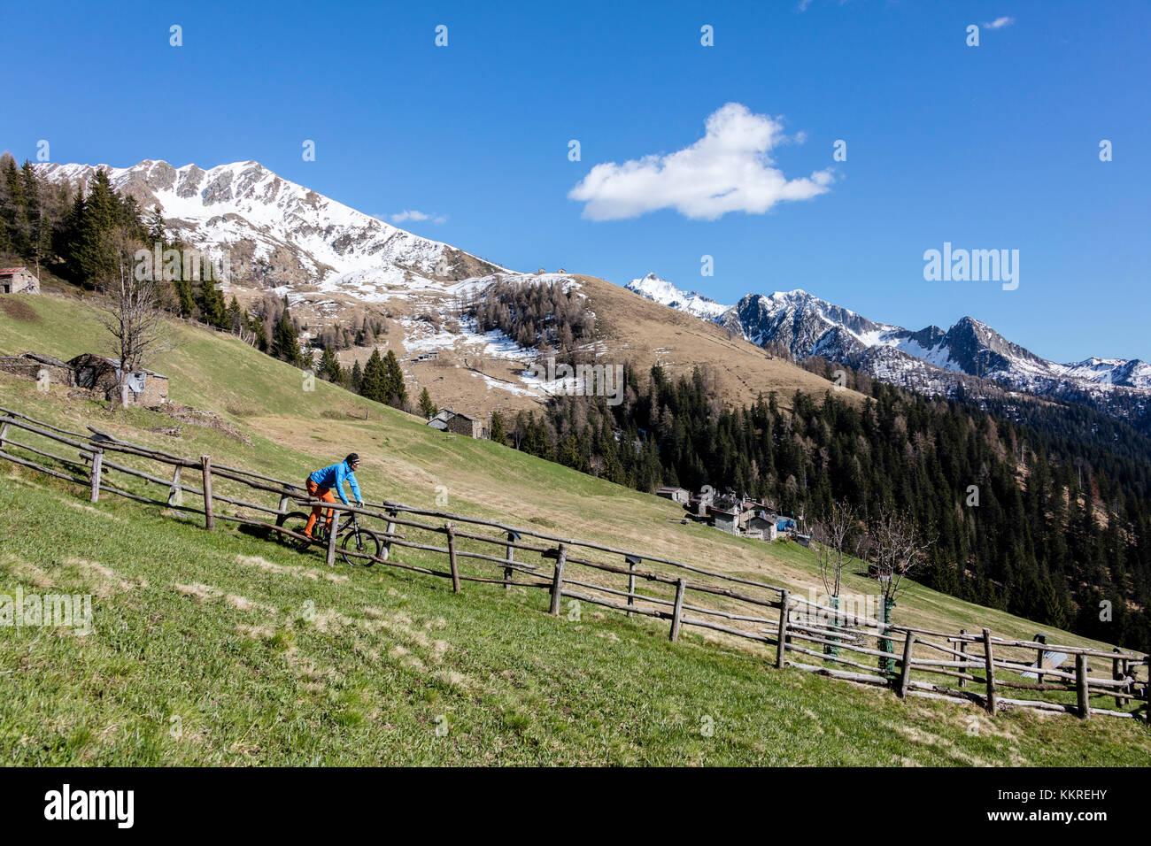 Mountain bike on green meadows framed by snowy peaks in spring Stock ...