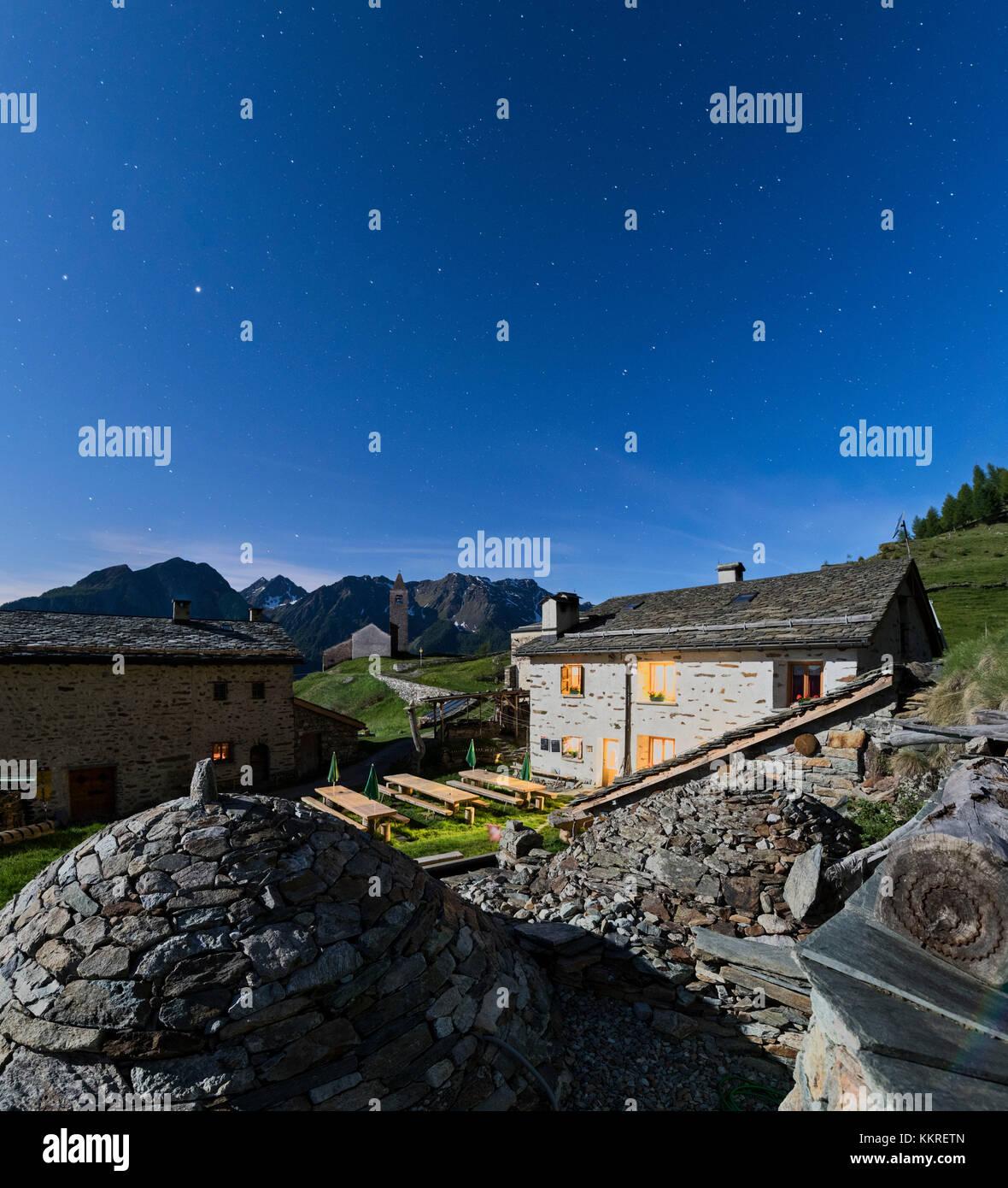 Panoramic of mountain retreat under starry sky, San Romerio Alp, Brusio, Canton of Graubünden, Poschiavo valley, - Stock Image