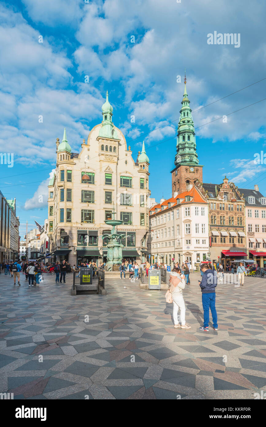 Copenhagen, Hovedstaden, Denmark. Tourists and bars in Amager square (Amagertorv) with St. Nicholas church in the - Stock Image