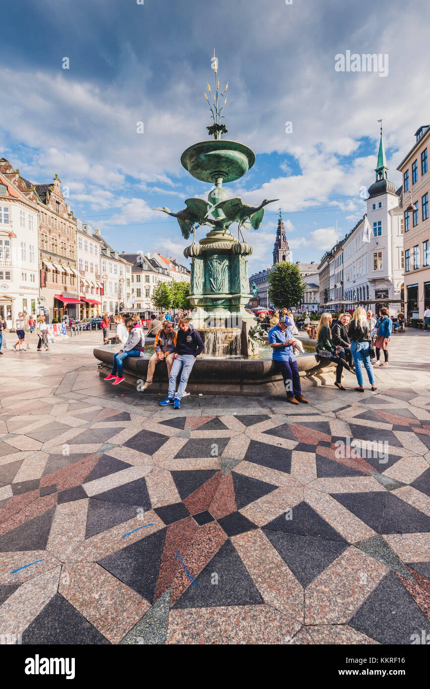 Copenhagen, Denmark. Tourists at the Storkespringvandet, or Stork Fountain in Amager square (Amagertorv). - Stock Image