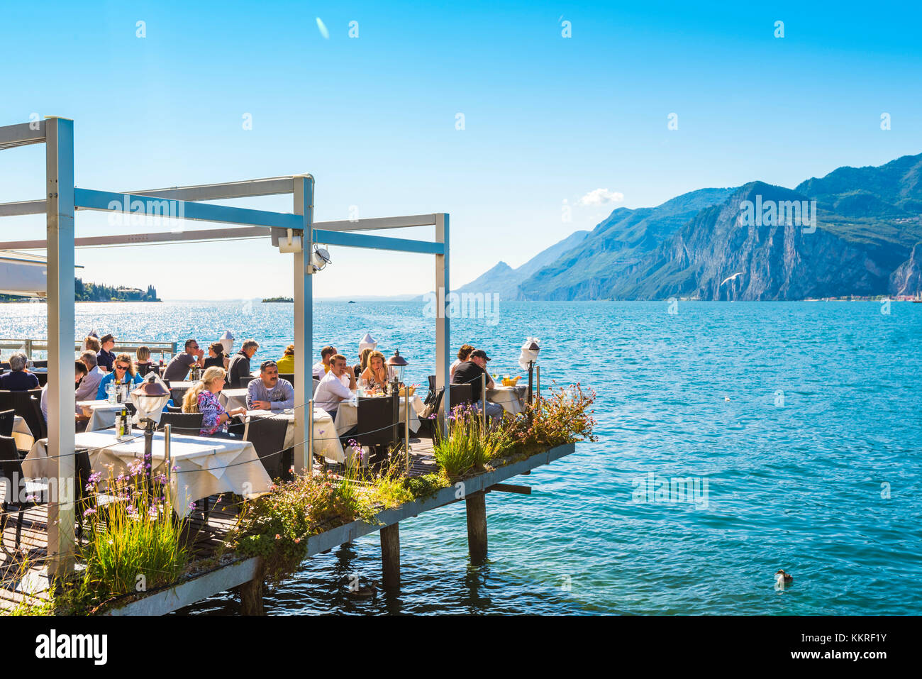Malcesine, lake Garda, Verona province, Veneto, Italy. Tourists eating out in a restaurant on water. Stock Photo