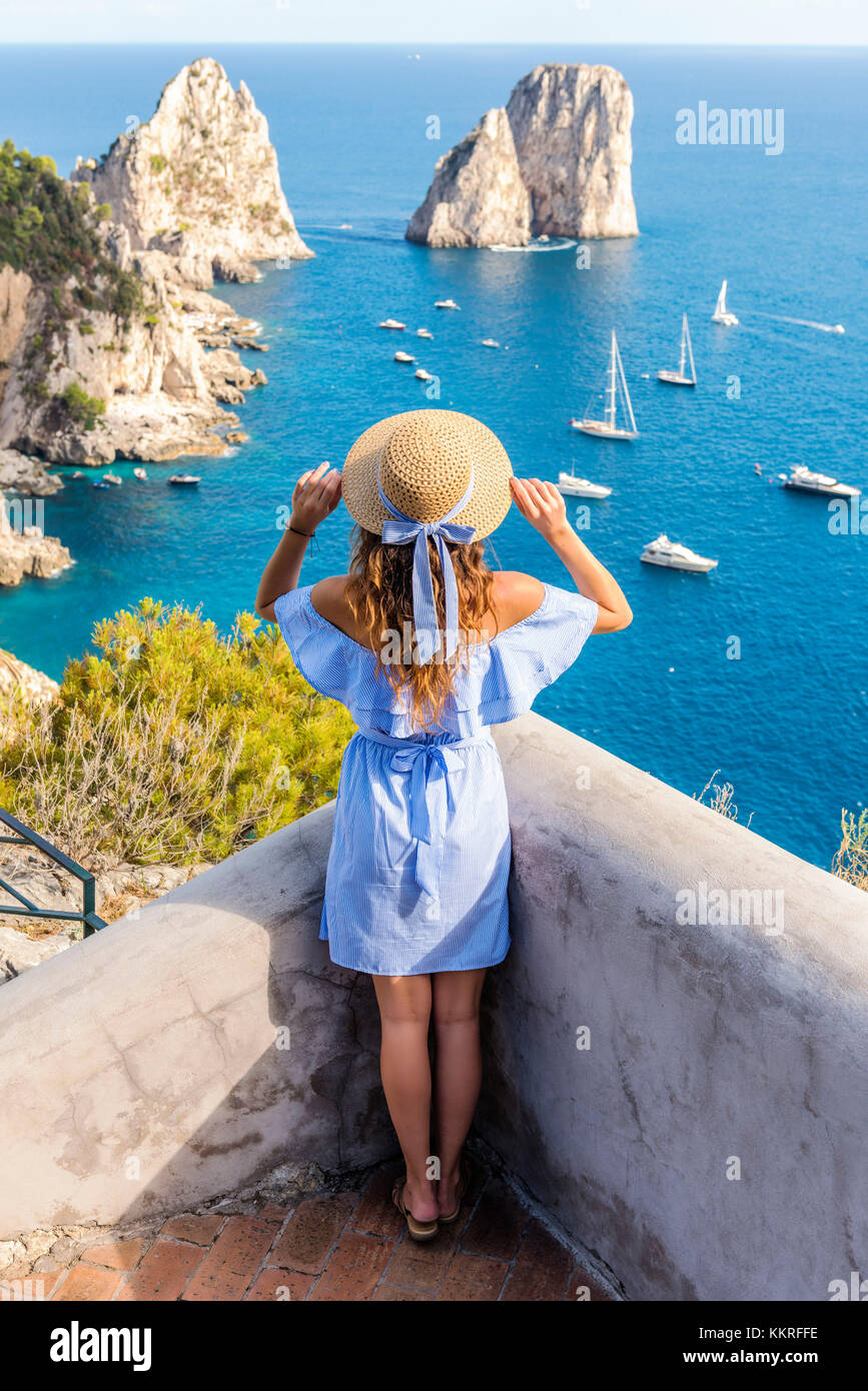 Capri, Naples, Campania, Italy. The cliffs of Capri seen from Belvedere cannone. A girl admiring the view - Stock Image