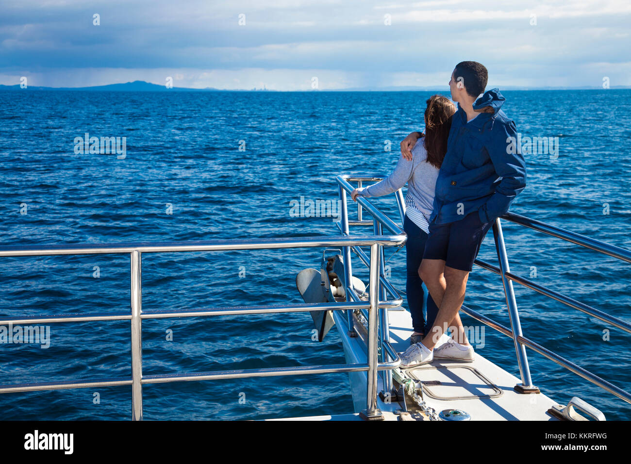 A couple embracing each other, looking out to sea on a cruise boat (Whale and Dolphin Safari, Auckland, New Zealand) - Stock Image