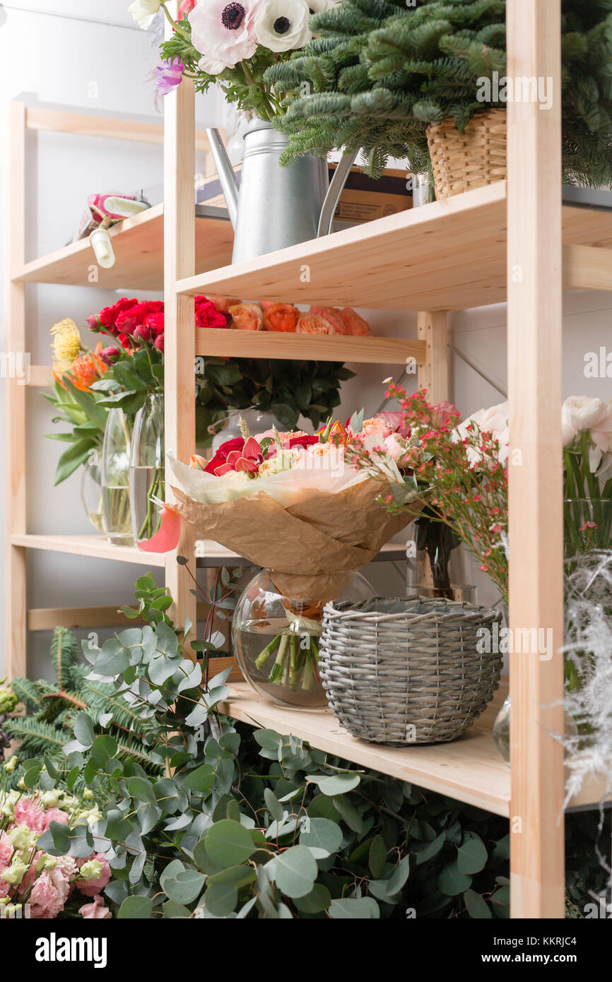 different varieties. Fresh spring flowers in refrigerator for flowers in flower shop. Bouquets on shelf, florist - Stock Image