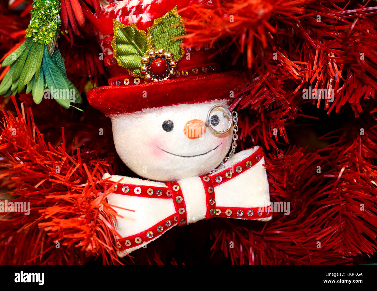 Steampunk snowman ornament with monacle top hat and bow tie on red Christmas tree - Stock Image