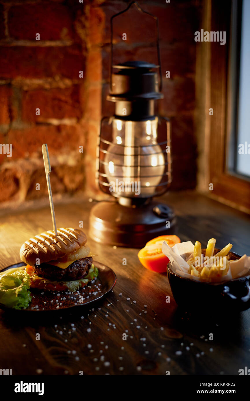 Wood top on her fries and Burger.The concept of the pub and fast food - Stock Image