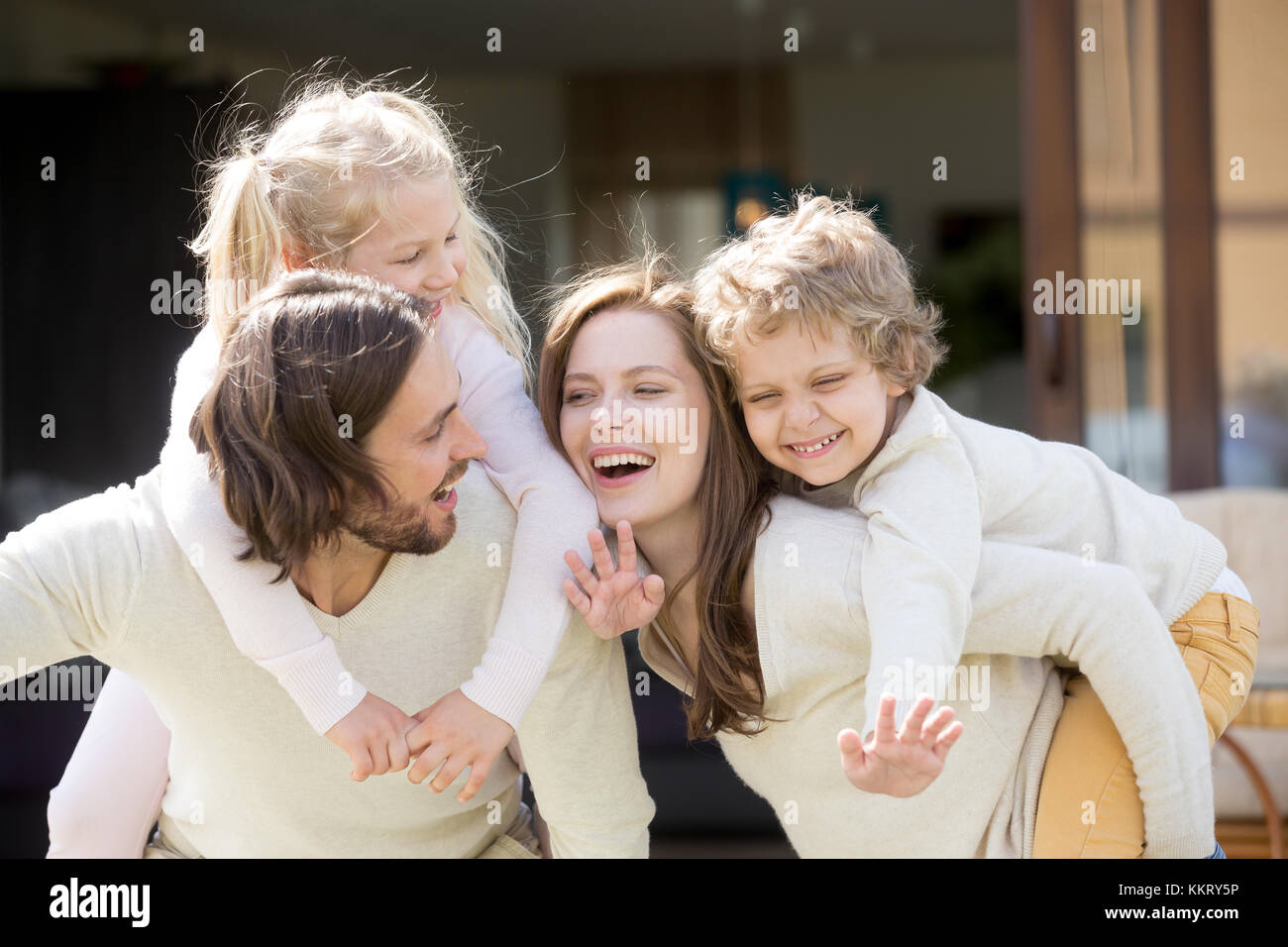 Happy smiling parents piggybacking son and daughter, family leis - Stock Image