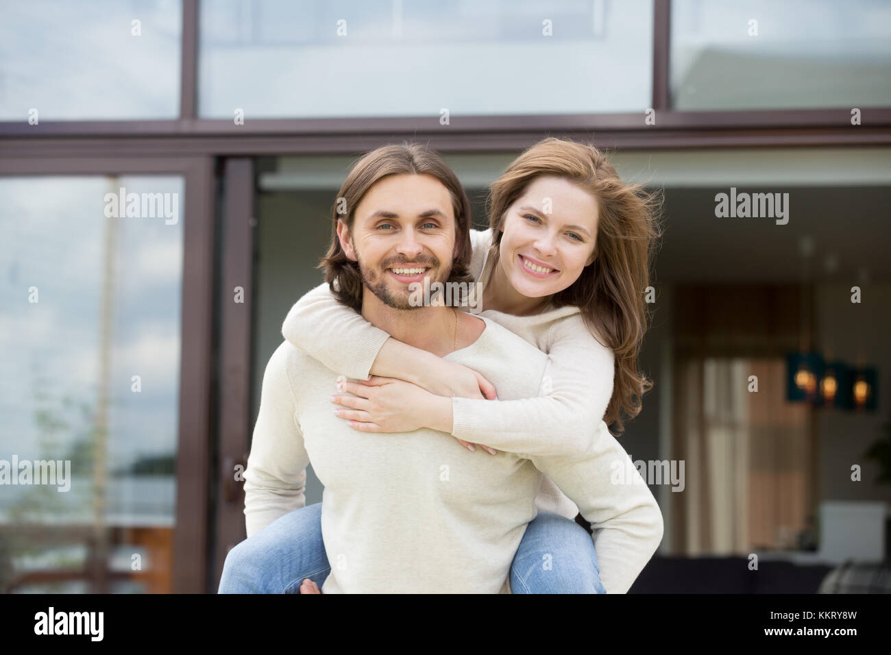 Man holding woman on back outdoors, looking at camera, portrait - Stock Image
