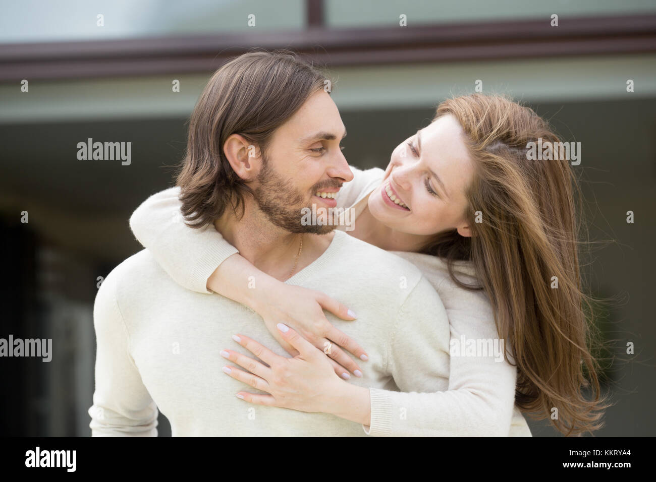 Young wife embracing husband from his back enjoying leisure outs - Stock Image