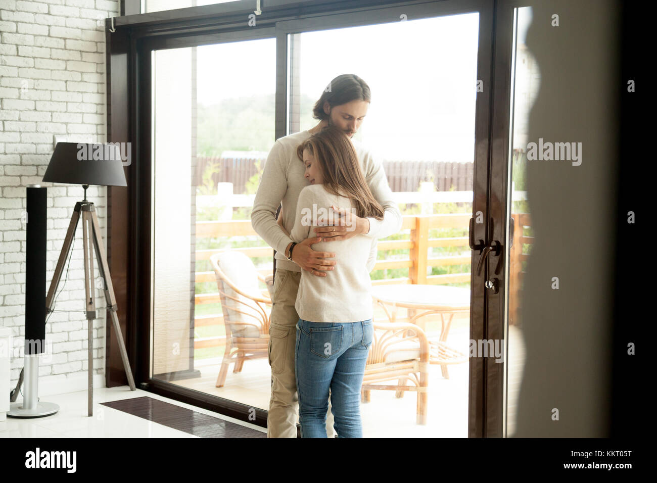 Young man and woman hugging standing at home, couple reconcilia Stock Photo