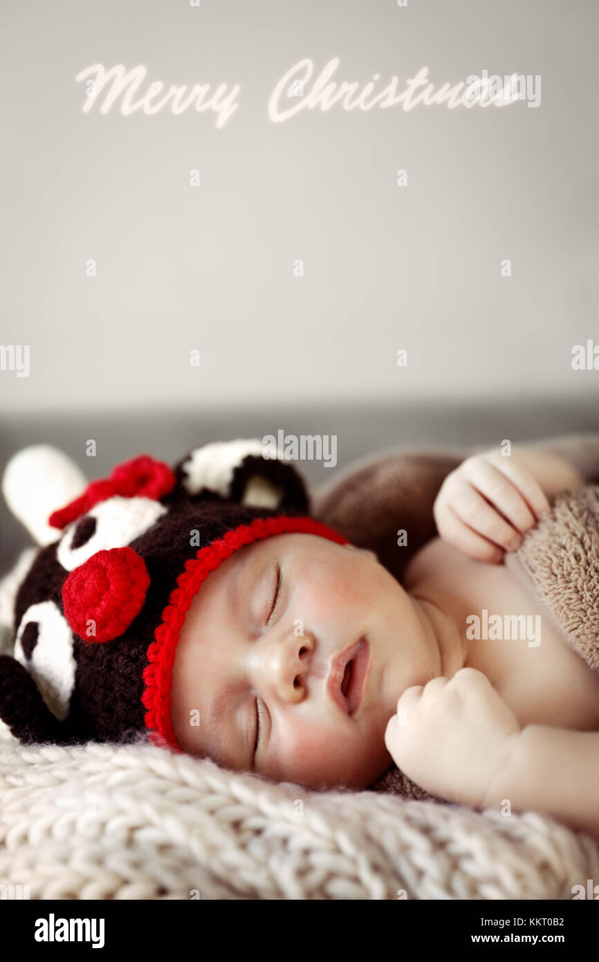 Closeup portrait  of a cute little baby boy sleeping at home wearing Christmas costume, cute reindeer hat, nice - Stock Image