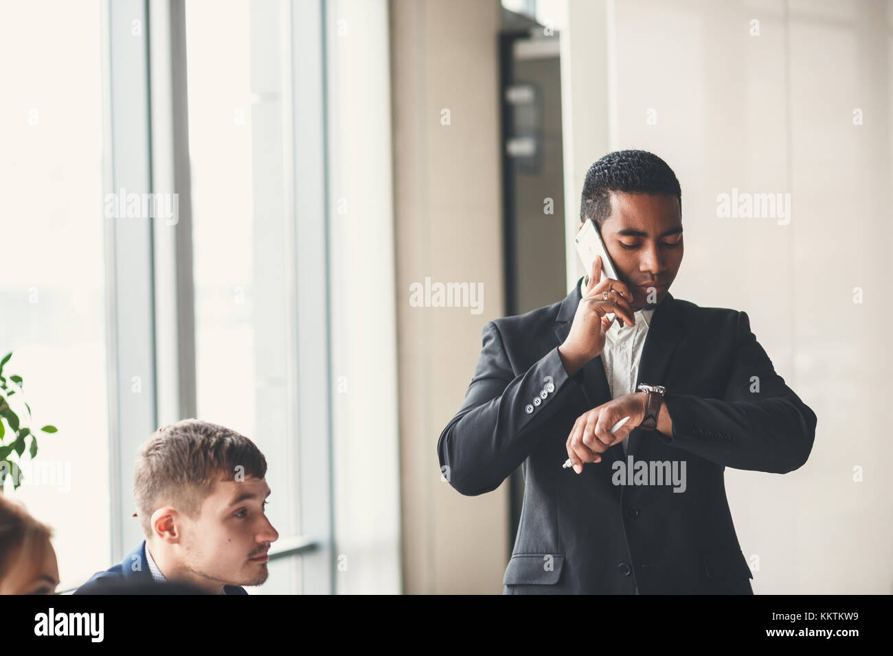 handsome african american businessman using smart phone emailing - Stock Image