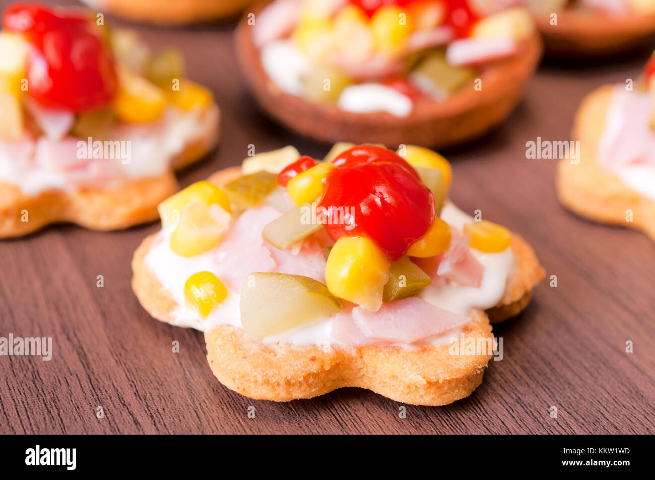 Small snacks with vegetables and ham on wooden table - Stock Image