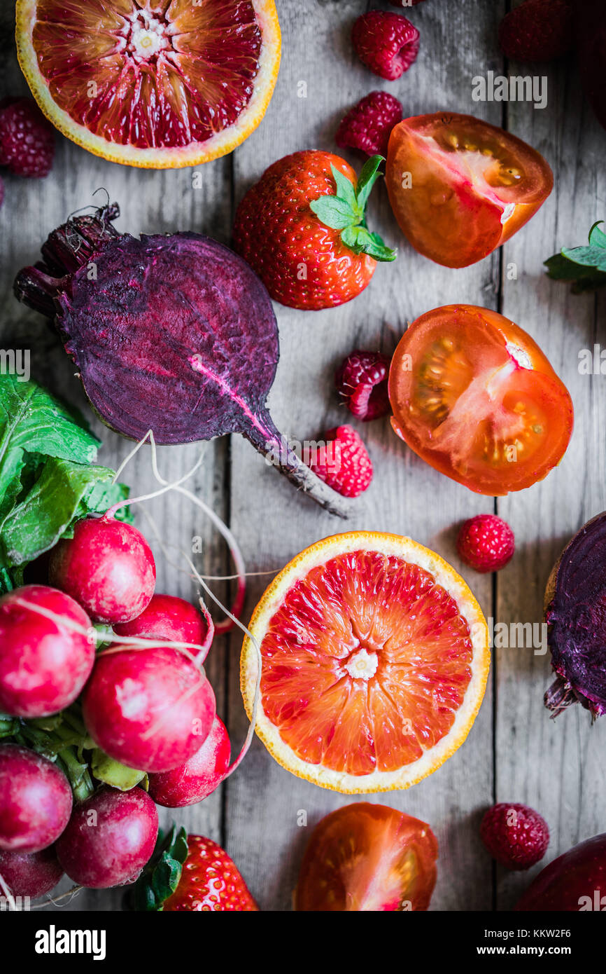 Red fruits and vegetables on wooden background - Stock Image
