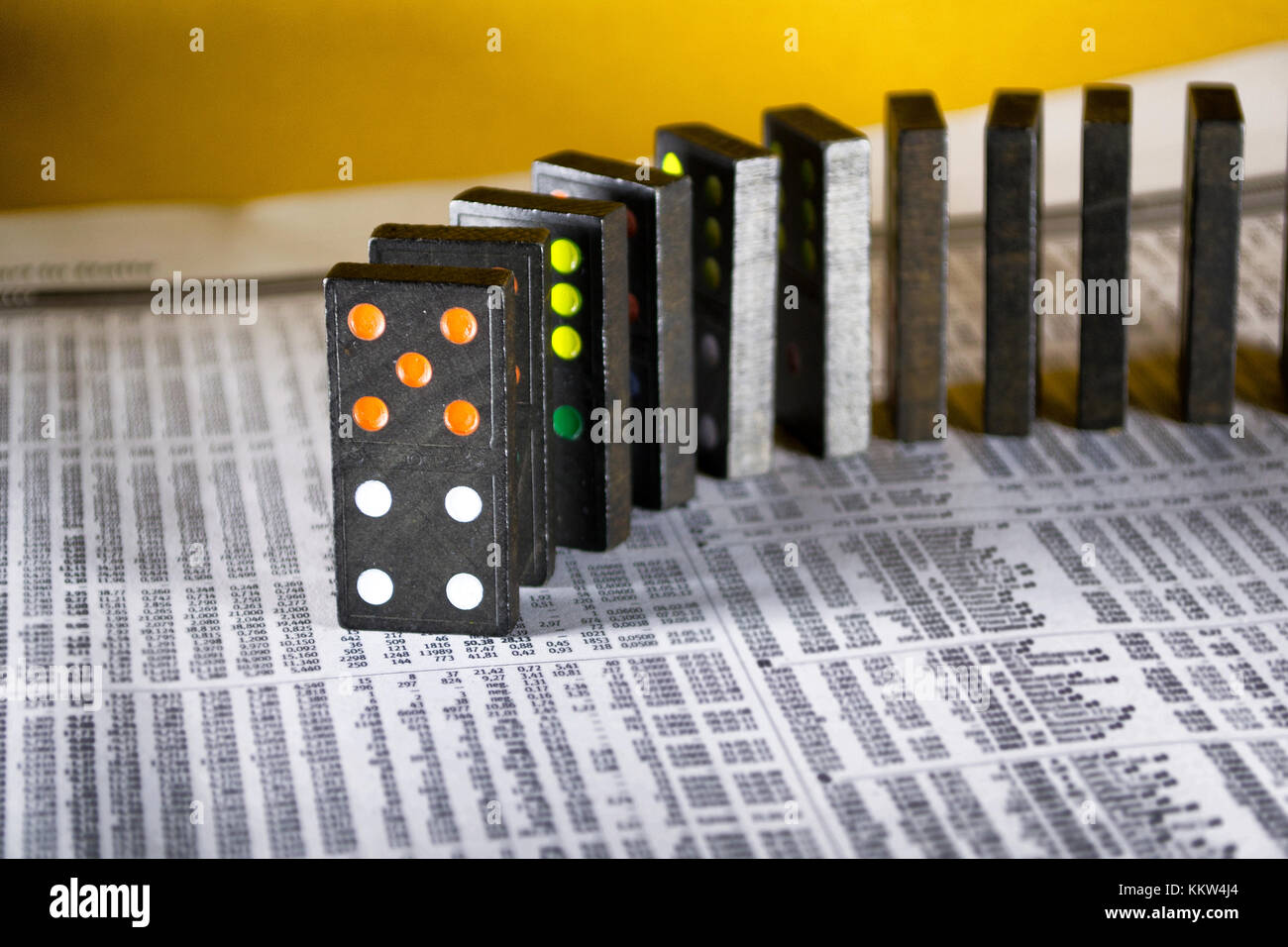 Domino on financial newspaper - Stock Image