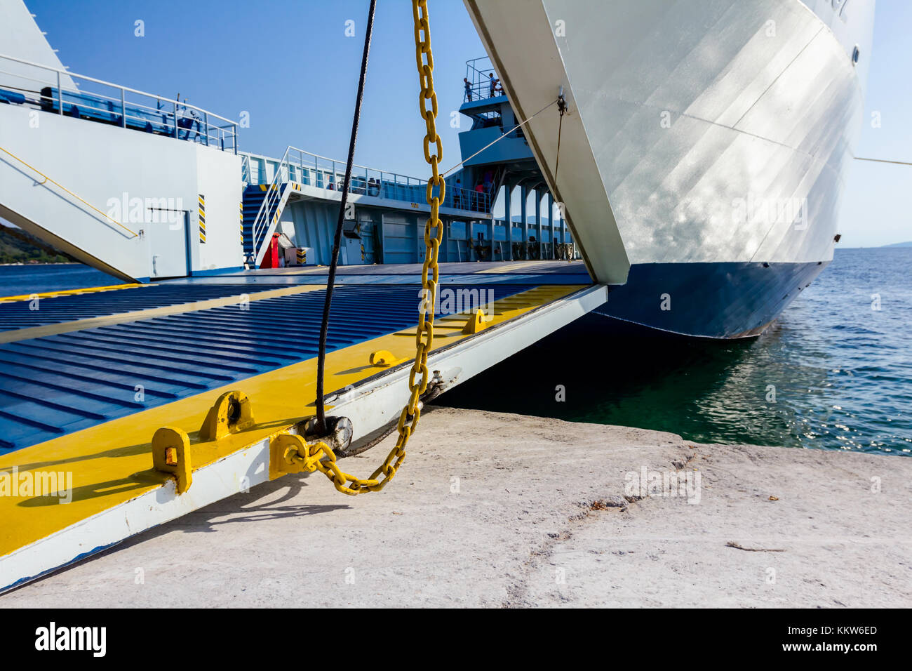Anchored large ferryboat has open front entrance at the local port. - Stock Image