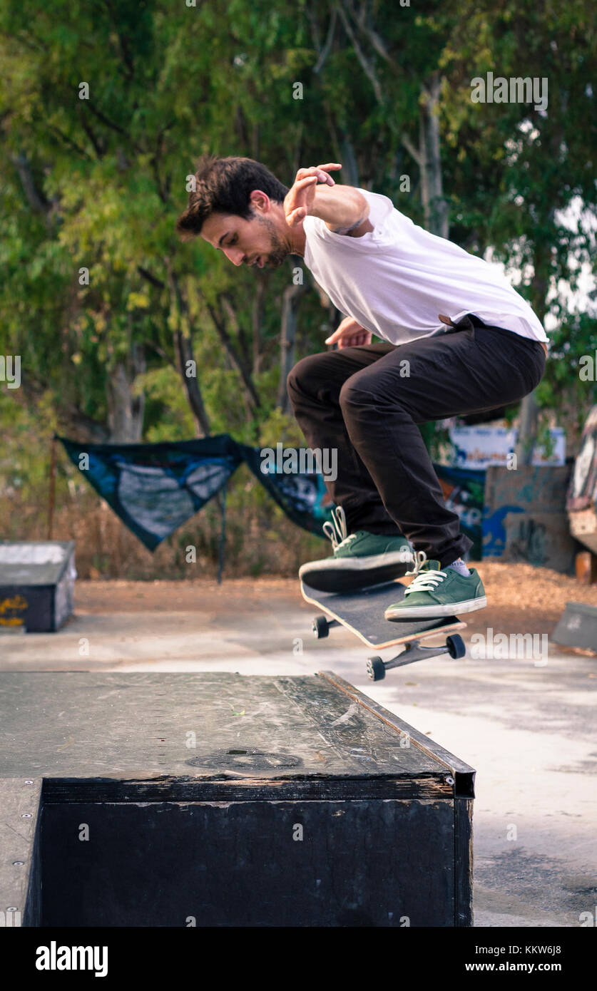 A young boy takes a ollie jump skate to climb over a step. - Stock Image