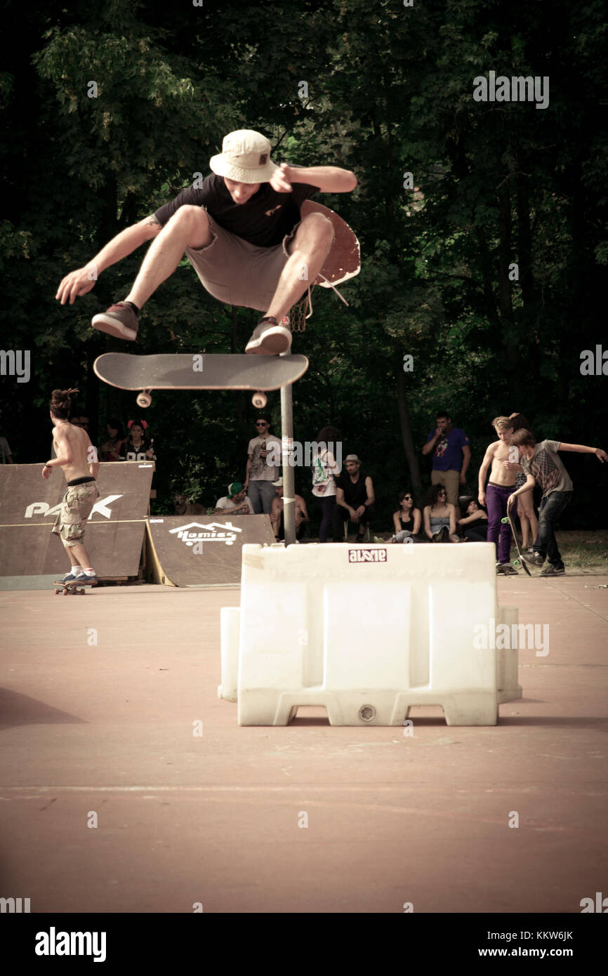 a guy jumps a hurdle with the skateboard----Savona, SV, Liguria, Italy - July 21, 2014: A young boy jumping on the - Stock Image