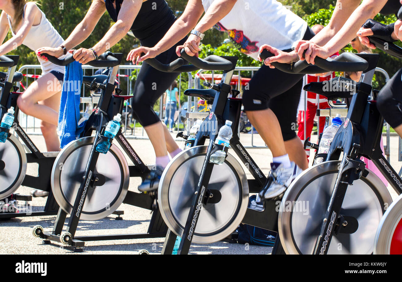 People who are riding on an exercise bike in a public urban park in Imperia. -----Imperia, IM, Italy - May 18, 2014: - Stock Image