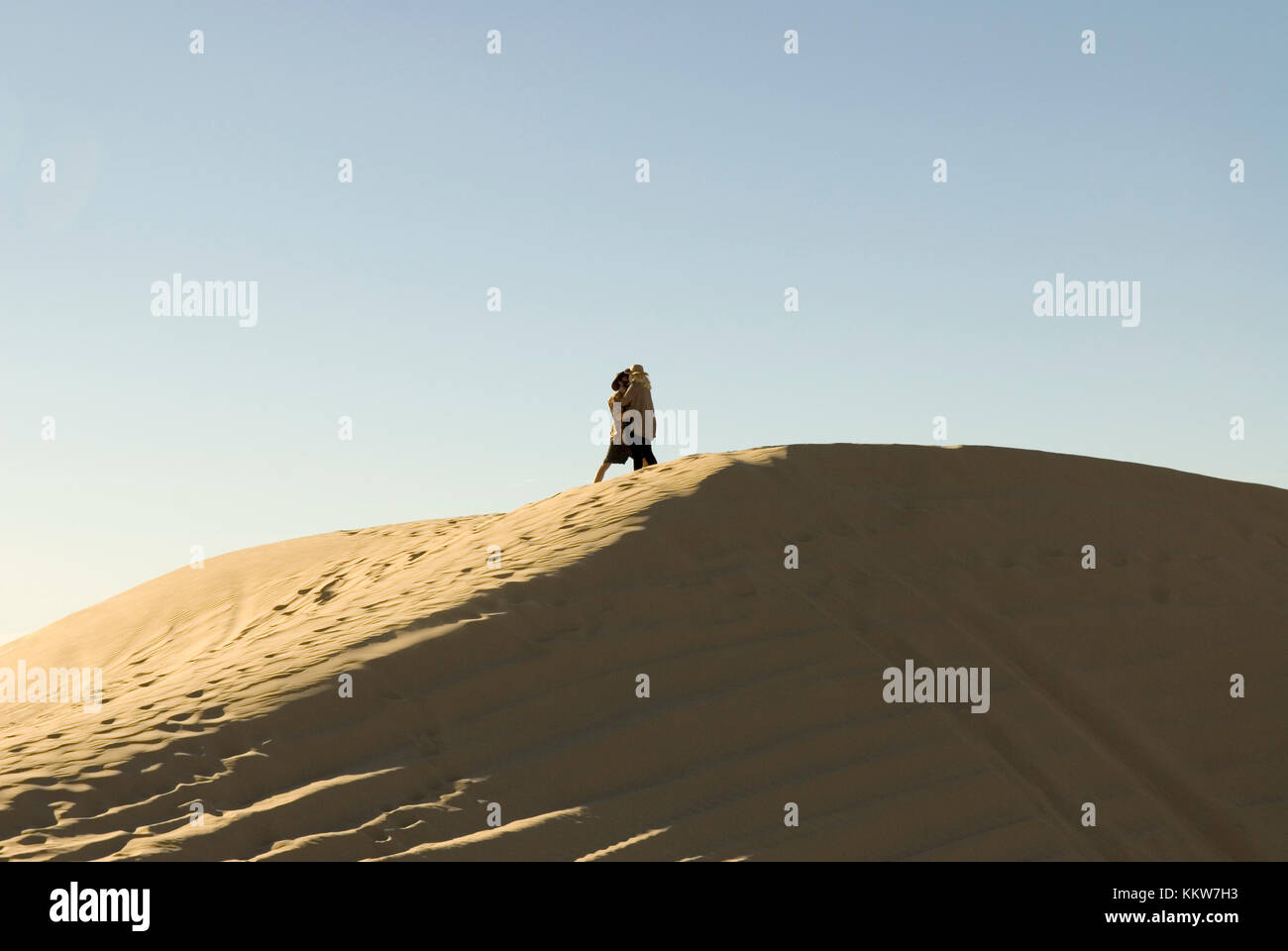 Couple kissing at Imperial Sand Dunes Recreational Area, California, USA. - Stock Image