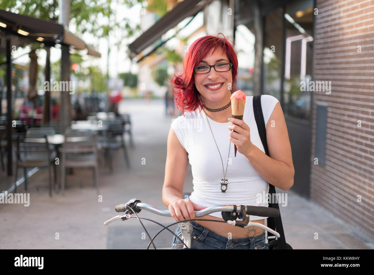 Young woman with ride bike in the city and eats ice cream in summer - Stock Image