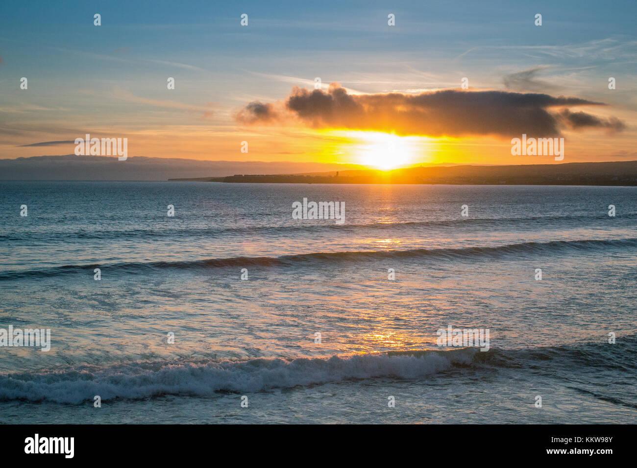 Sunset over Atlantic Ocean in little surf town in Ireland - Stock Image