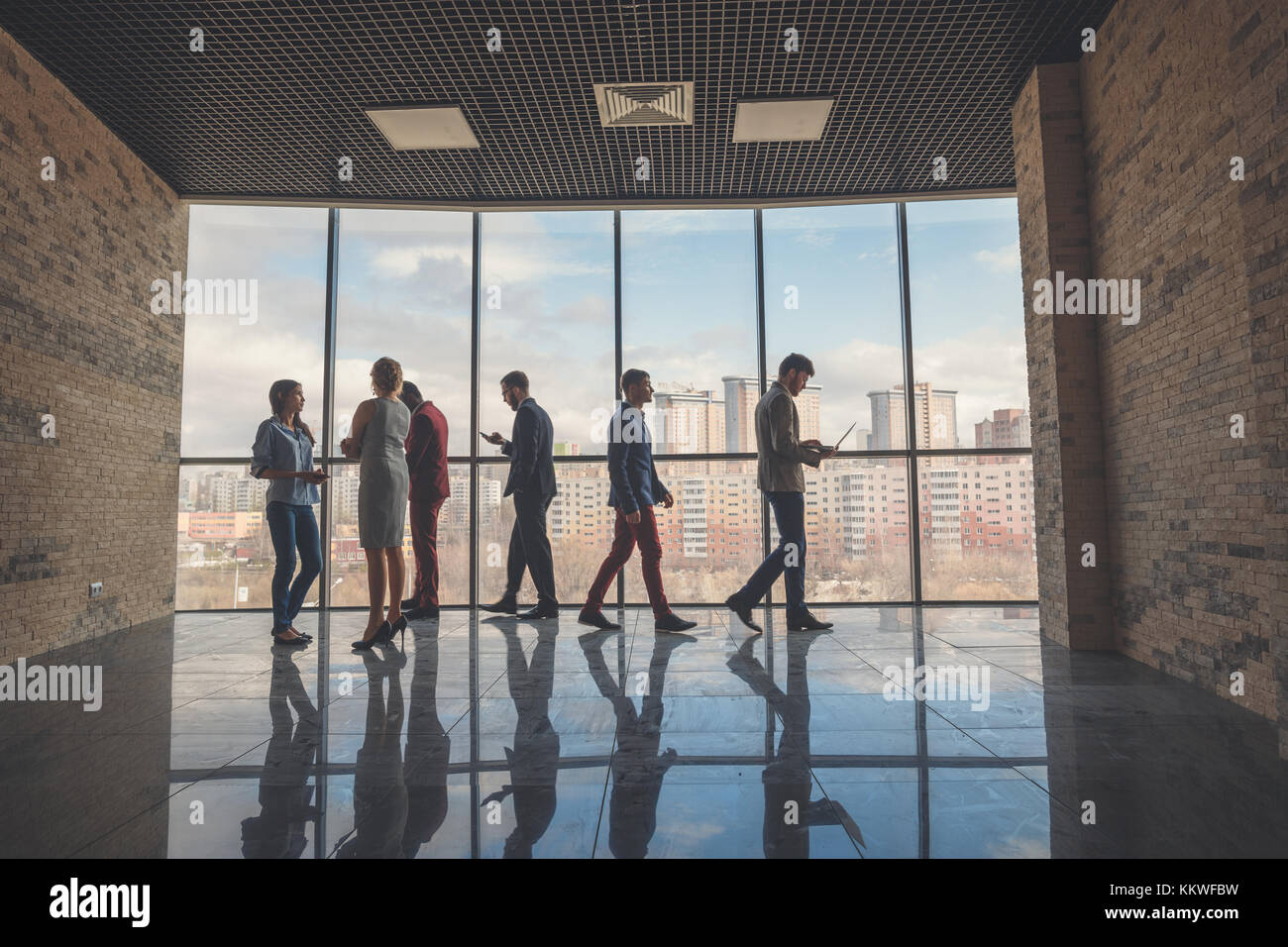Silhouettes of business people in a conference room. - Stock Image