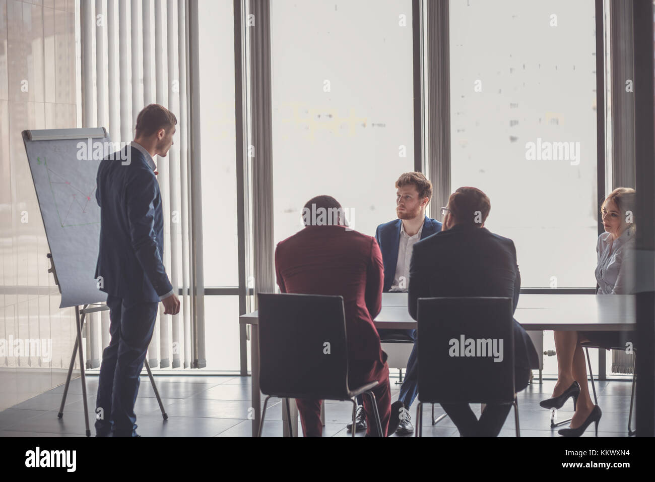 Business plan explained on flipchart by CEO to colleagues - Stock Image