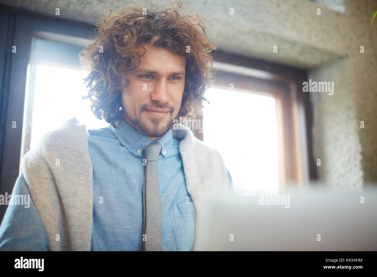 Young man in formalwear looking at laptop display during work - Stock Image