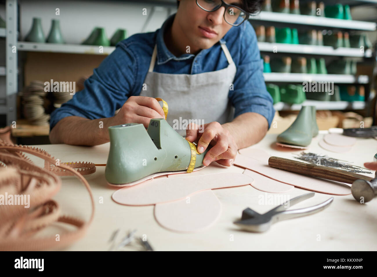 Contemporary cobbler measuring boot workpiece on table in his workshop - Stock Image