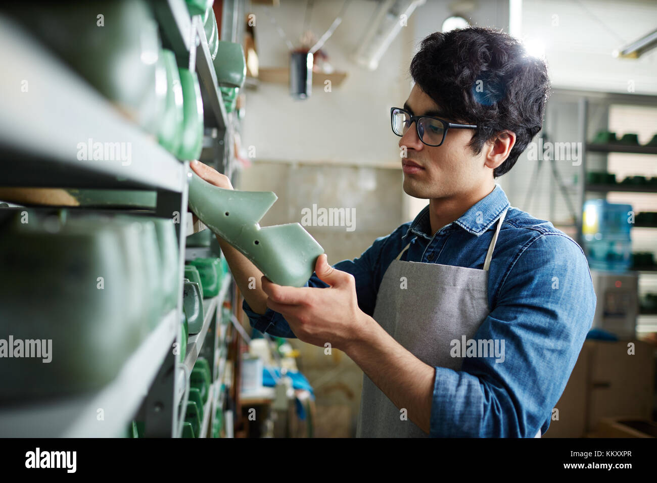 Young shoemaker taking one of footwear workpieces from shelf - Stock Image