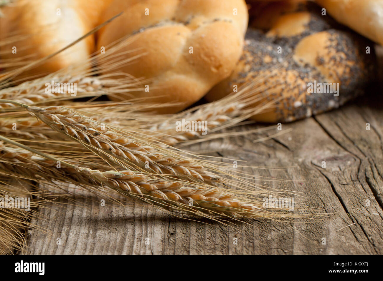 Dried ears of corn on old wooden table with fresh bread as background - Stock Image