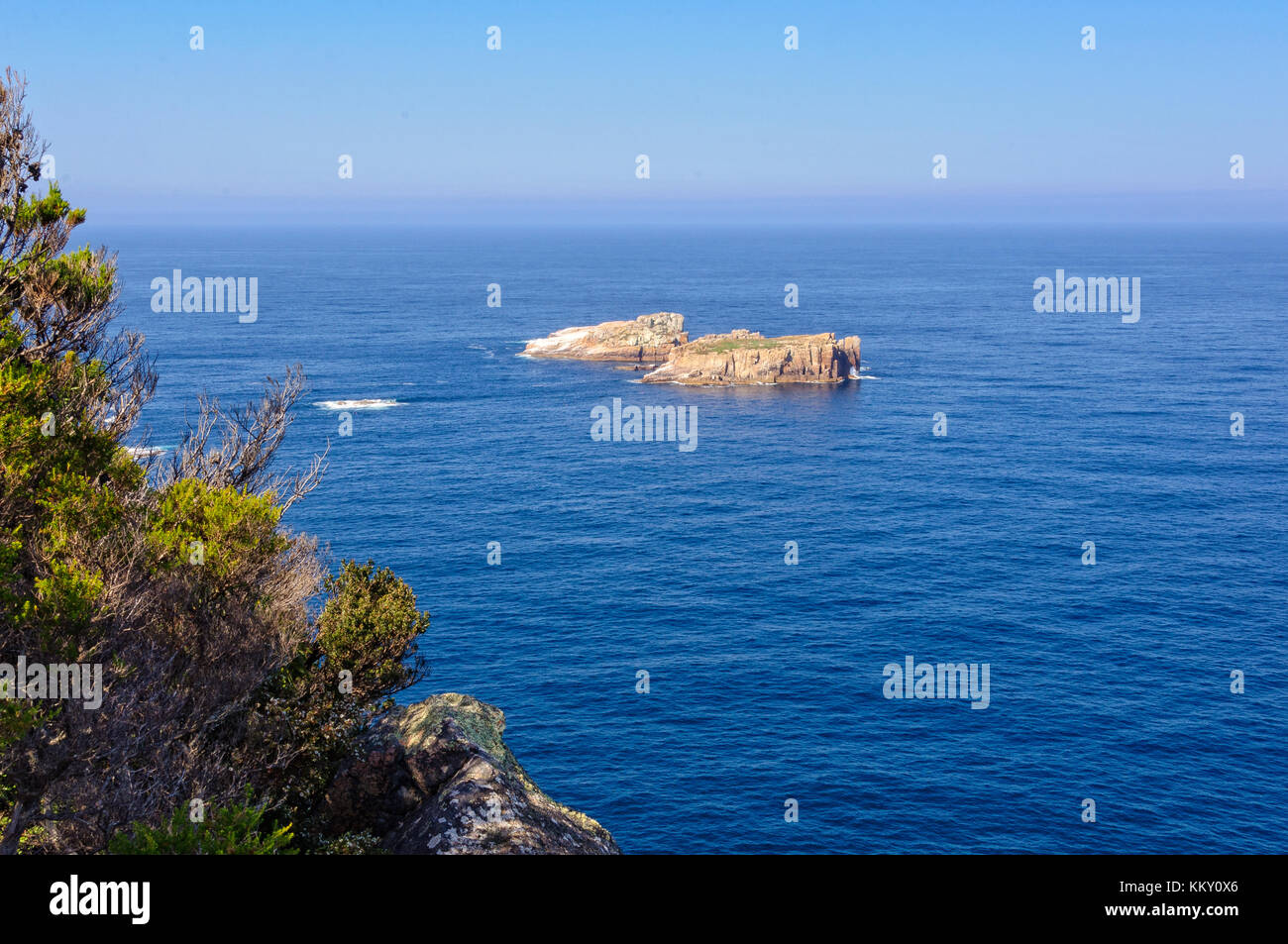 Two small rocky islands surrounded by blue water below the Cape Tourville Lighthouse in the Freycinet National Park Stock Photo