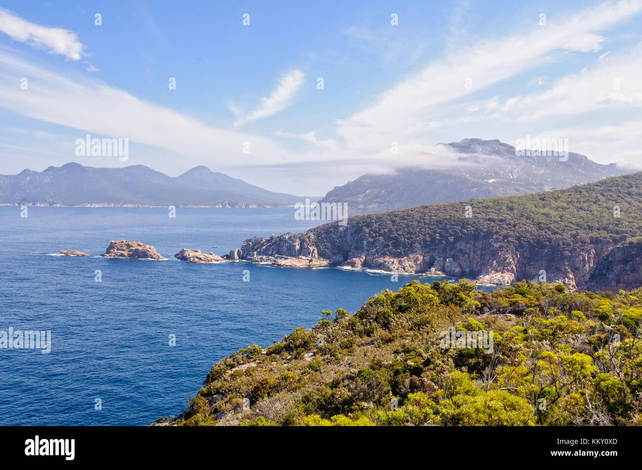 Light clouds over Carp Bay and The Hazards in the Freycinet National Park - Tasmania, Australia - Stock Image