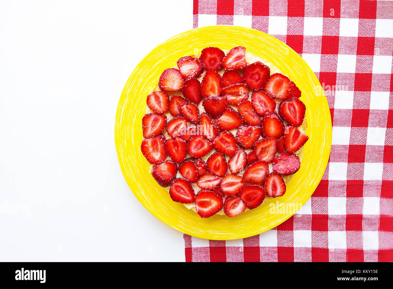 Bright and delicious strawberry cake on a red napkin in a cage - Stock Image
