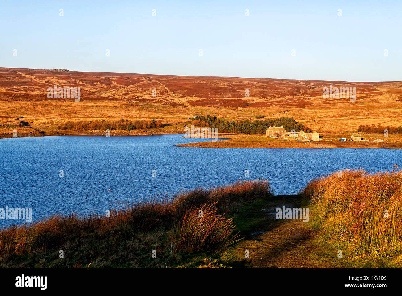 Grimwith reservoir in the Yorkshire Dales National Park bathed in the late afternoon sun on a cold autumn day. Stock Photo
