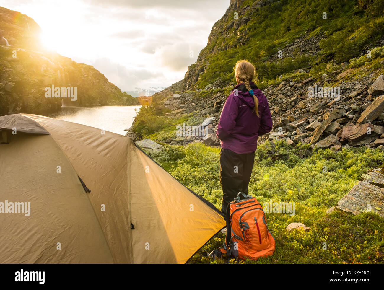 tourist tent and woman near mountain lake, summertime sunset, Norway - Stock Image