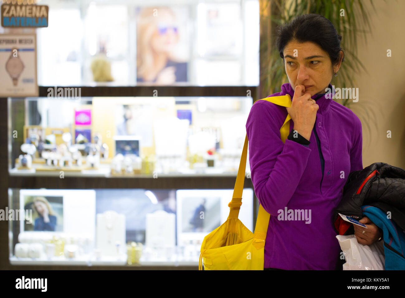 Woman tired of shopping during Christmas time in shopping mall in Belgrade Serbia - Stock Image