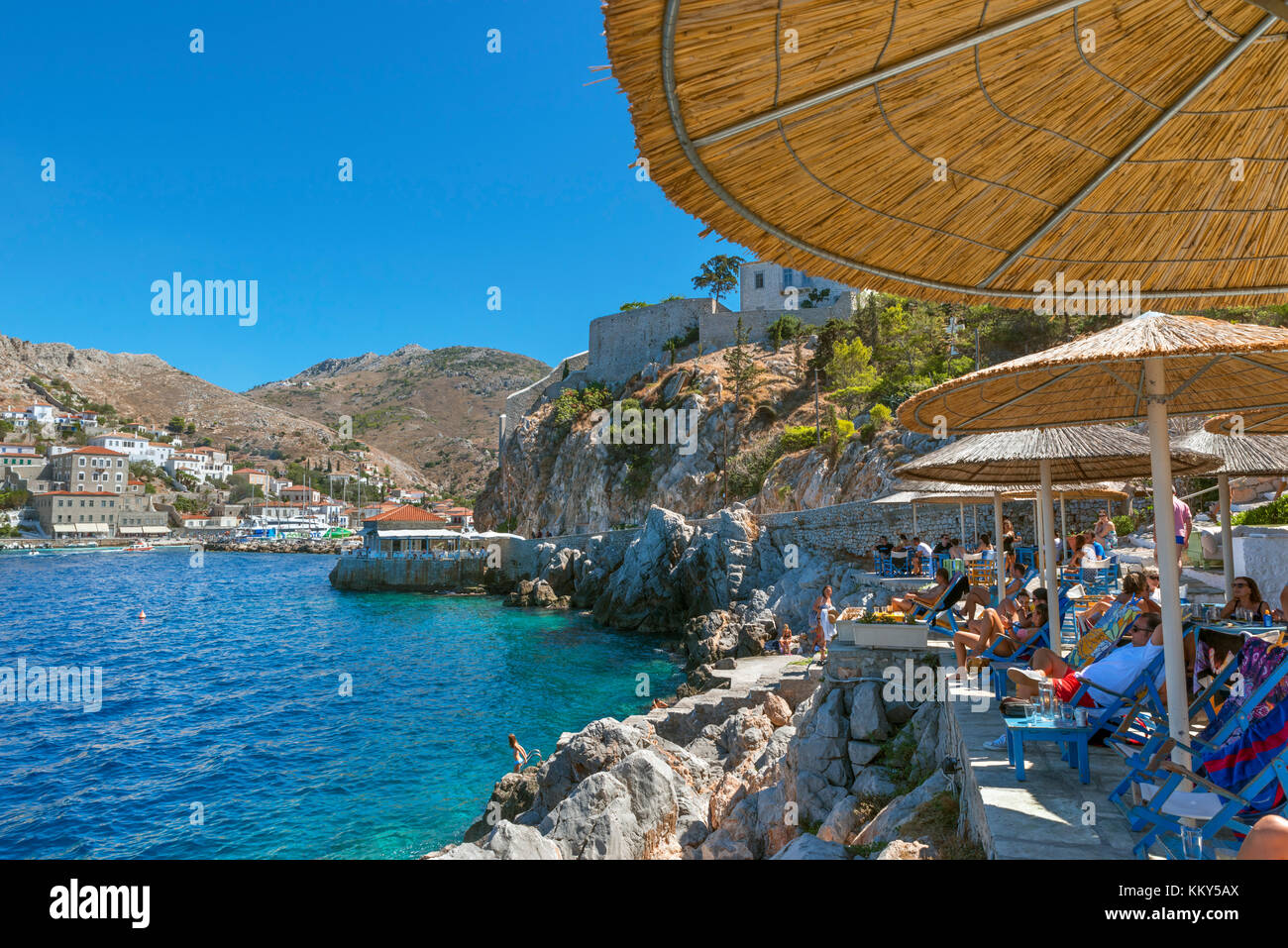 Seafront bar and bathing area just outside Hydra Town, Hydra, Greece - Stock Image